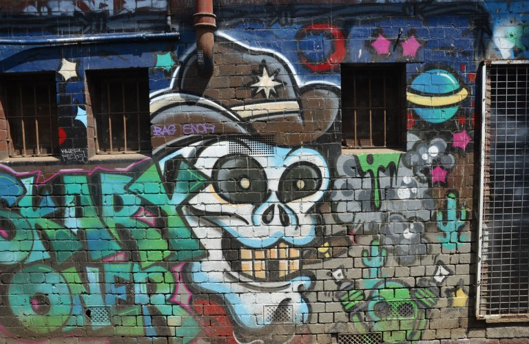 "white skull wearing a brown cowboy hat amongst graffiti tags on a brick wall. words ""scary oner"" written to the left of the skull"