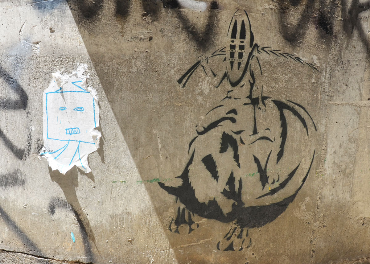Two street art pieces. On the right is a black stencil of a person wearing an African mask and holding a branch behind his head. He is sitting on the back of an animal. on the left is a simplistic drawing of a square face with two little stick legs