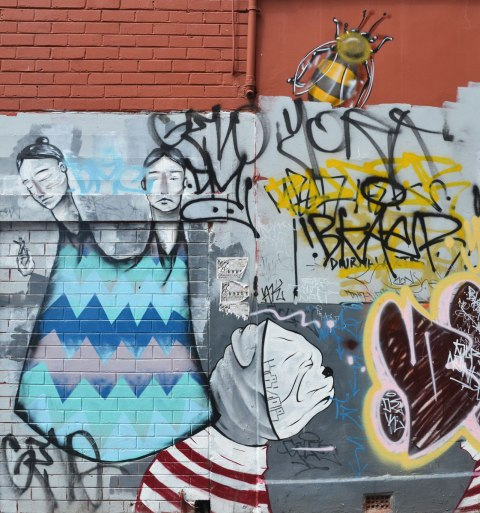 street art of a person with two heads wearing a long blue dress with no arms or legs visible but with one hand holding a very small person, also a large bumblebee street art painting. also a dog wearing a red and white striped top and a white dog face mask