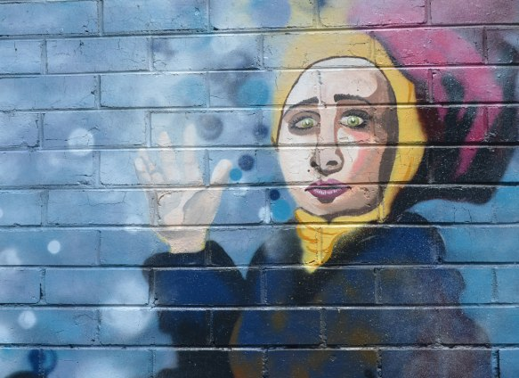 street art painting of a woman in a yellow head scarf and blue top waving