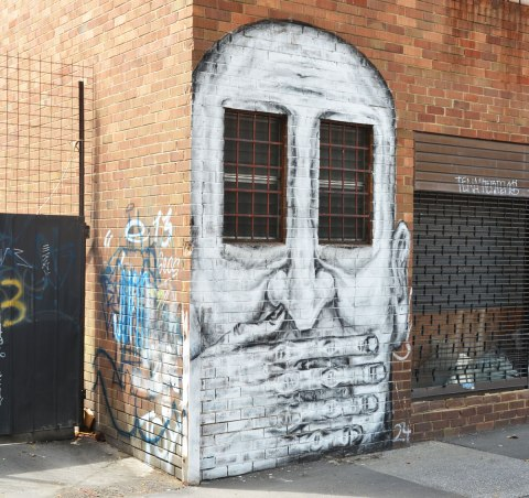 street art painting of a large white man's face with two windows as eyes, his hand is over his mouth
