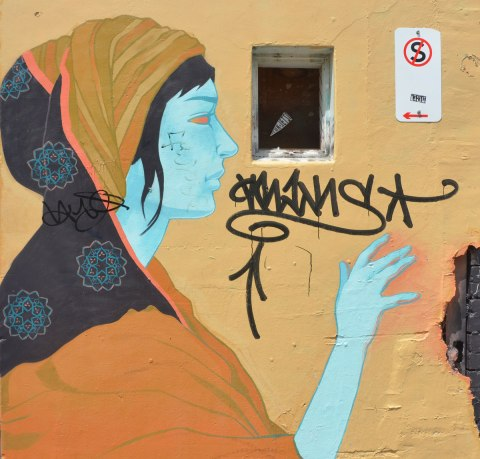 street art painting in Melbourne of a woman with light blue skin, an orange top and a two patterned head scarf, orange and gold stripes and black with blue and pink circular patterns on it.
