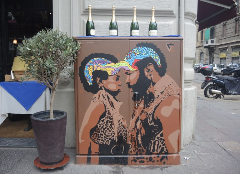metal box on a sidewalk outside of a restaurant in Milan, painted brown with a picture of two black people, a man and boy, both with curly afro hair styles painted in rainbow colours. They are facing each other, nose to nose. 4 wine bottles are on top of the box.