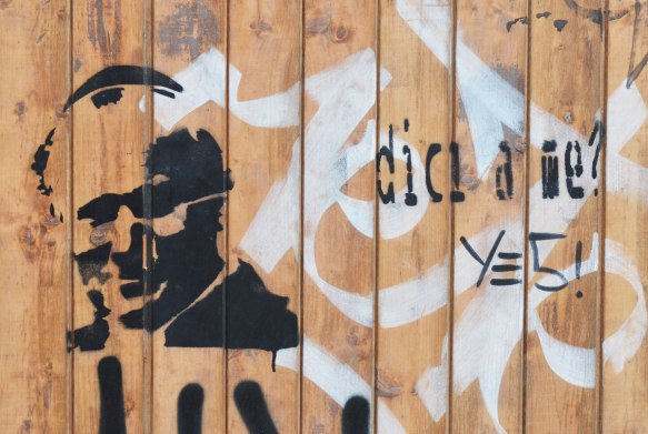 "black stencil of the pope's head and shoulders on a brown wood wall. The words ""dici a me"" are stenciled on too."