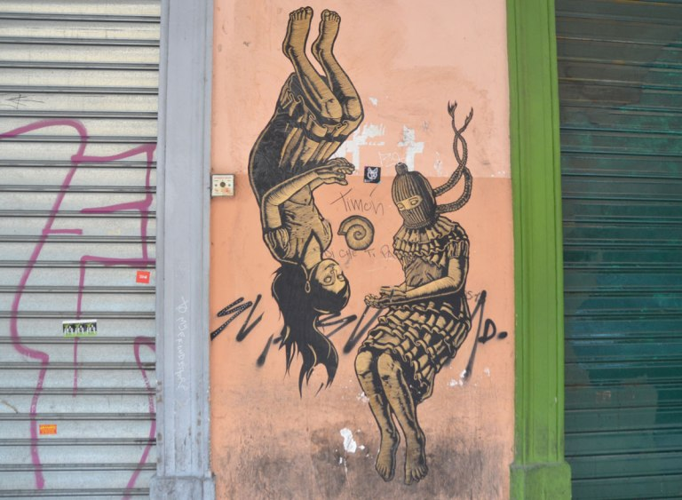 pasteup on a salmon coloured door with a green wall on one side and a grey metal shutter on the other. The pasteup is of two women, one is upside down.
