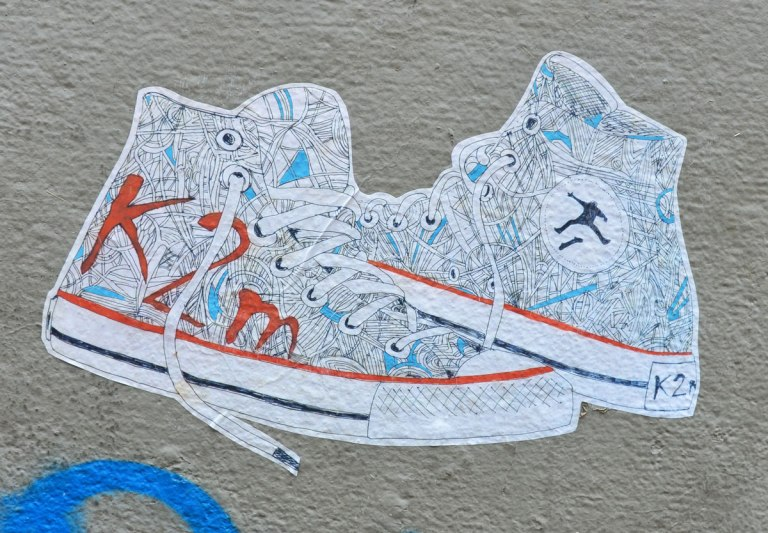 street art paste up of white high top rinning shoes with K2m written on the side in large red letters. The shoes are covered with what looks like drawings of yarn and balls of yarn
