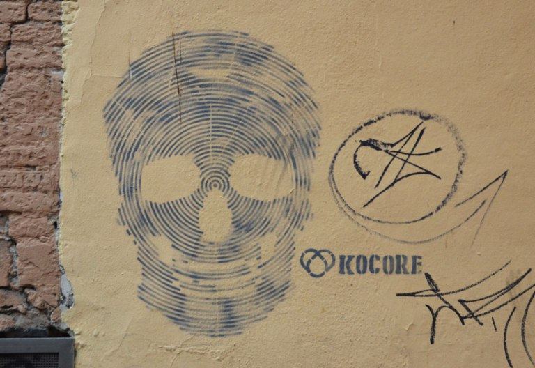 street art piece of a skull made up of lots of grey lines The word Kocore is beside the skull