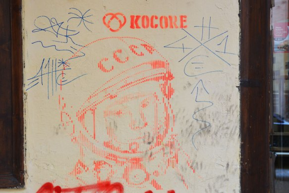 a street art piece in orange by kocore of the head of a Soviet cosmonaut with his helmet on.