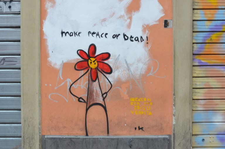 "Small painting of a stick figure with its hands on its hips. Its face is a flower, looks like a red daisy with 6 petals. The words "" make peace or dead are written above"