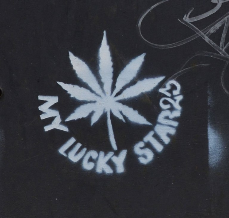 white stencil on black of leaf from marijuana plant with the words my lucky star23 written aroud it. On black background