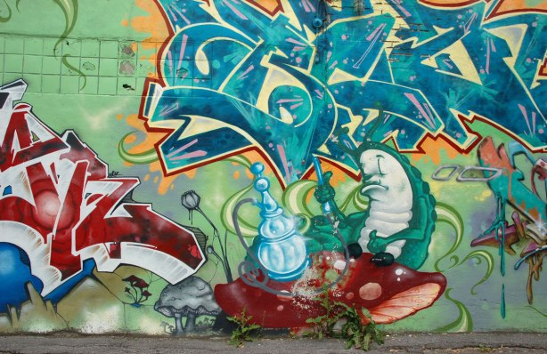 part of an Alice in Wonderland mural in a Montreal alley, looking down along the wall that the mural is on - a sleepy fat caterpillar sitting beside a large light blue hookah
