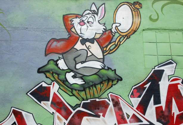 part of an Alice in Wonderland mural in a Montreal alley, looking down along the wall that the mural is on - an anxious looking white rabbit with a large pocket watch in his hand, wearing black bowtie