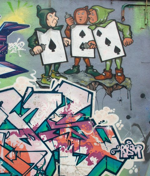 part of an Alice in Wonderland mural in a Montreal alley, looking down along the wall that the mural is on - three playing cards, the Ace, 2 and 3 of spades, as young men in black caps and tights, large cards for their bodies