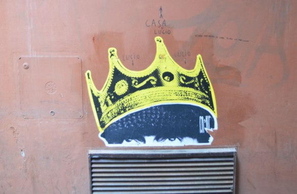 paste up of yellow crown on a young man's head. The graffiti has been placed above a metal feature on a concrete wall so the eyes look like they are peering over it. Someone has written the words Casa Lucio with an arrow pointing upwards above the crown.