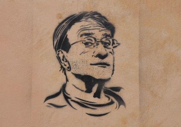 black stencil of Robin Williams on a wall, graffiti