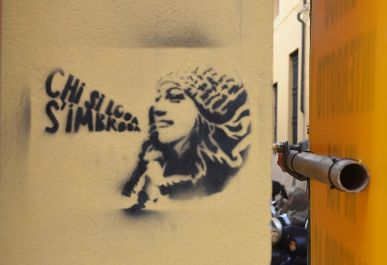 "black stencil of a woman's head in profile, long hair, wearing a hat, words coming out of her mouth, shape of words is a megaphone. Words say "" Chi si loda s'imbroda"""