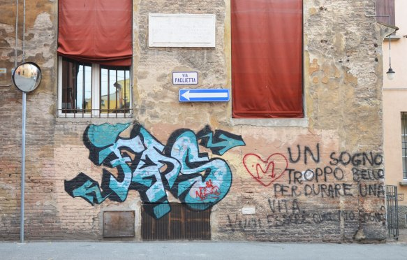 graffiti on an old stone building with burgundy coloured window shades, blue tag, other words written on the wall include