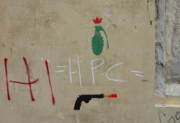 Two small stencils on a wall, a green hand grenade and a black handgun,