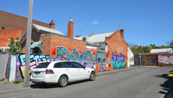 a white car is parked on a street in front of a long wall with street art on it, two tags, or text graffiti and a ghetto blaster painting.