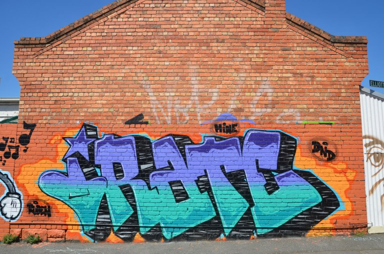 large text graffiti that says IRATE, purple on the top and blue on the bottom, on a brick wall on the side of a building.