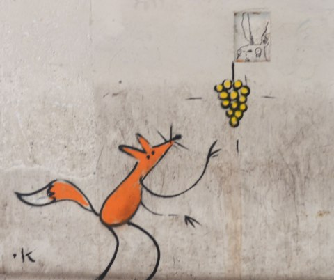 graffiti on a concrete wall, an orange fox reaches for a bunch of yellow grapes that are higher on the wall