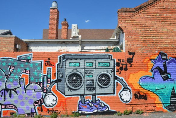 a street art painting of a ghetto blaster with speakers that look like round eye, tiny legs with sneakers and arms with big white hands.
