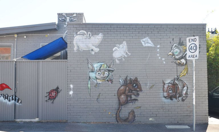 a mural of an assortment of animals on a grey wall. a ladybug, two flying pigs,