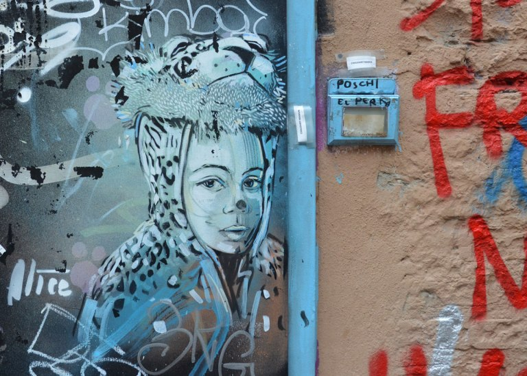 bluish grey graffiti paingint on a wall of a child (head and shoulders) wearing a leopard costume, but with the mask lifted up so child's face shows, on a door