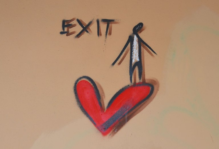graffiti on a beige wall, a stick drawing of a person stands on the upper right part of a red heart. The word exit is written above the left side of the heart