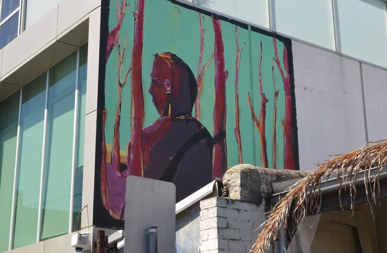 mural up high on the side of a building, a man amongst magenta trees.