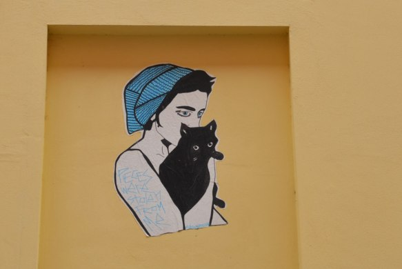 "a paste up of a person with short black hair, a blue hat and blue eyes, holding a black cat. On the person's arm, written in blue are the words ""Pieces were stolen from me"""