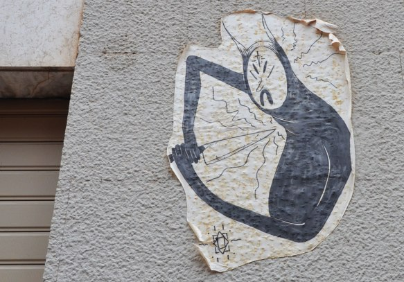 a paste up with slightly curled edges, graffiti on a concrete wall, a black picture of a man like creature with stylized features is pointing a large knife at its chest.