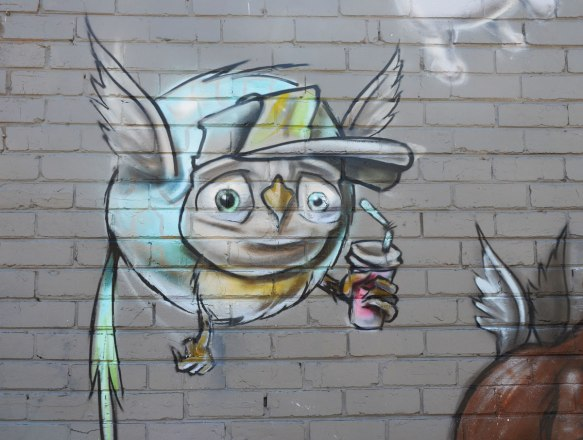 flying creature with bird body and human face, holding a drink with a straw in one hand.