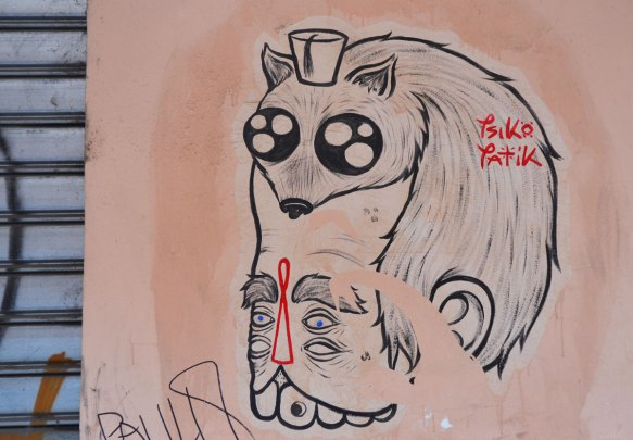 a grey tone graffiti on a pinkish wall, a small furry animal with a fez on its head and eyes that resemble nuclear symbols, sits atop a man's head. he has two sets of eyes and a large mouth with teeth