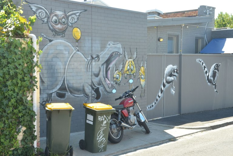 two garbage bins and a motorcycle in front of a mural on a grey wall. Mural is of a large rhino with its mouth open, trying to catch birds in its mouth, two leaping lemurs and leaping away from the rhinocerous.