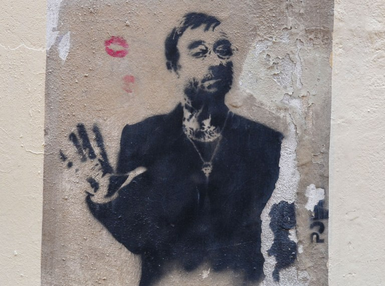 stencil in black on a concrete wall that is not in good shape, a man, from the waist up wearing a black jacket and a necklace. One hand is raised to shoulder level, showing palm. Over one shoulder are two red lip marks