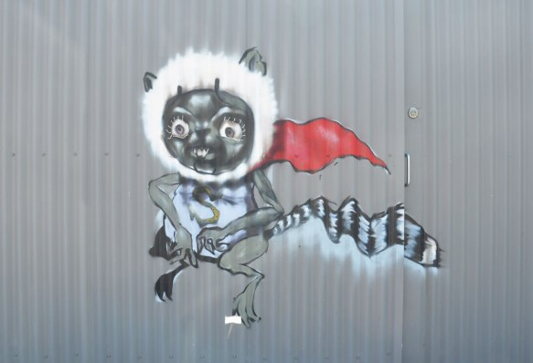 street art painting of an animal with a black and white striped tail, wearing a fuzzy white band around its head, and a red cape. Also wearing a shirt with a big S on it.