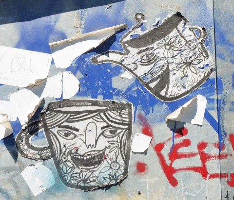 Two paper paste-ups, a teapot and a mug. Both have faces on them. The teapot is pouring tea into the mug.