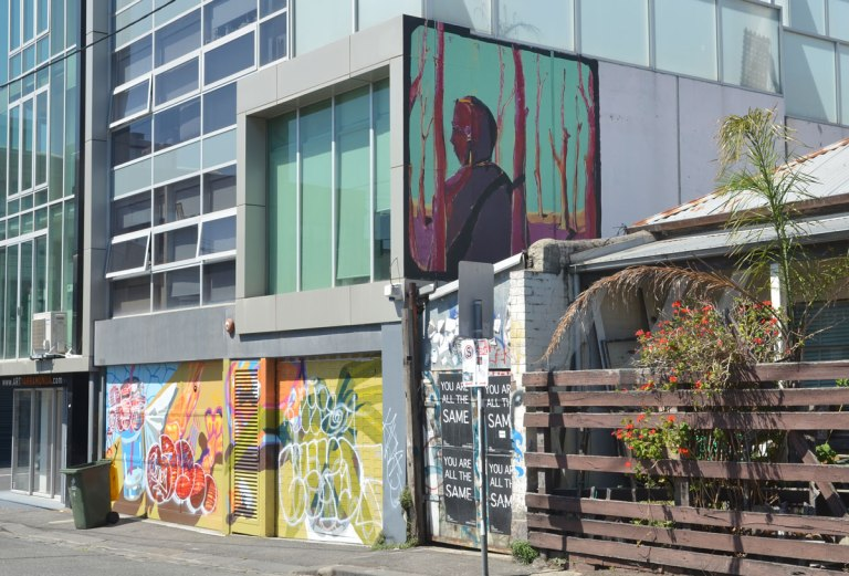 mural up high on the side of abuilding, a man amongst magenta trees. below it are two garage doors covered with graffiti