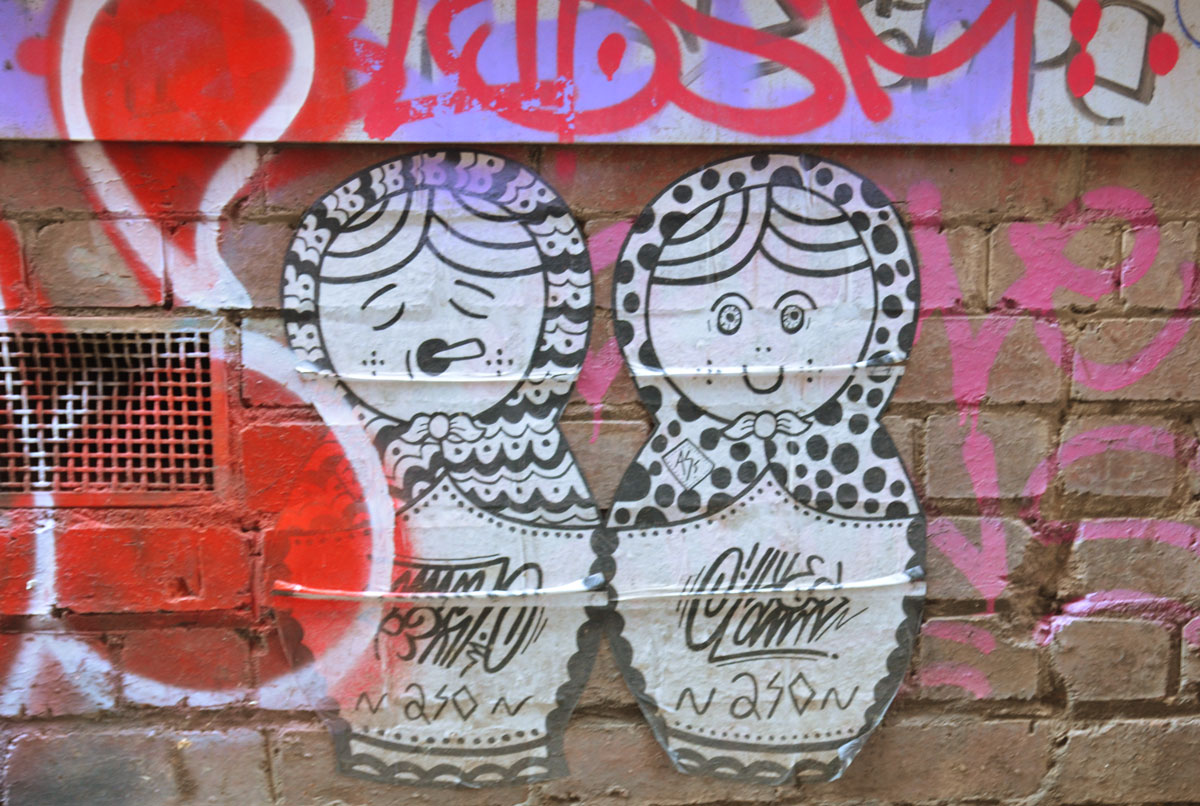 2 large paper paste ups of babushka doll shaped women. One with eyes open and smiling and the other with eyes closed.
