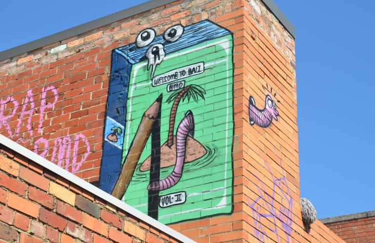 muralby BMD on the upper level of a red brick building. Cigarette box shaped box, front is green with a picture of an little island with one little palm tree and a large earthworm coming out of the sand. a large pencil is seen drawing the picture