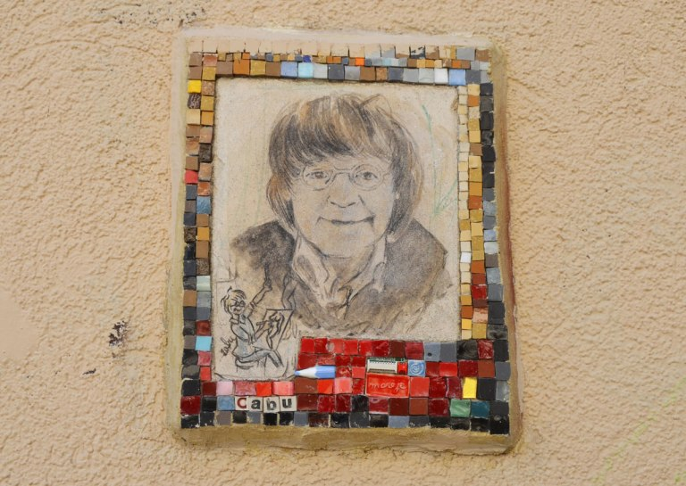small portrait of a man on a wall.  Hand drawn head and shoulder shot, framed with tiny pieces of mosaic tile - Cabo