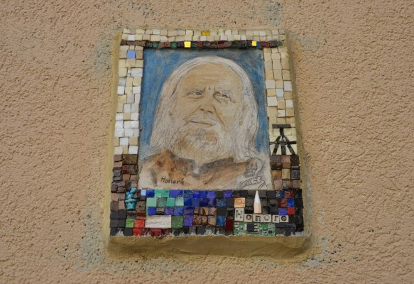 small portrait of a man on a wall.  Hand drawn head and shoulder shot, framed with tiny pieces of mosaic tile - Honore