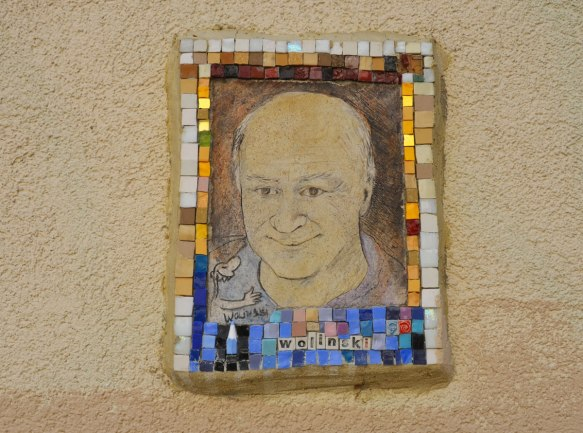small portrait of a man on a wall.  Hand drawn head and shoulder shot, framed with tiny pieces of mosaic tile - Wollinski