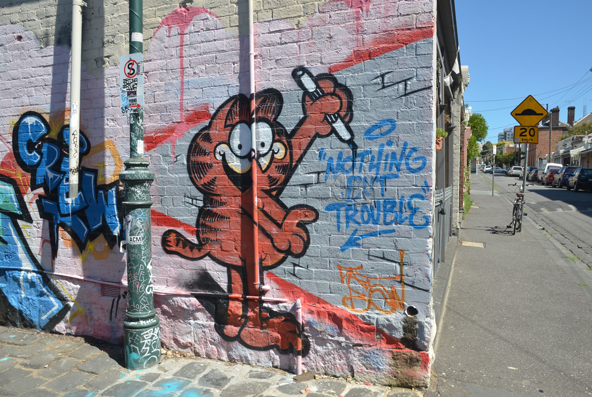 street art mural of Garfield the Cat holding a marker and writing on the wall, Nothing but Trouble