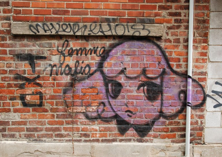 Starchild Stela character, a girl with shoulder length and slightly curly hair, painted in pink on a red brick wall with the words femme malia written in cursive beside it