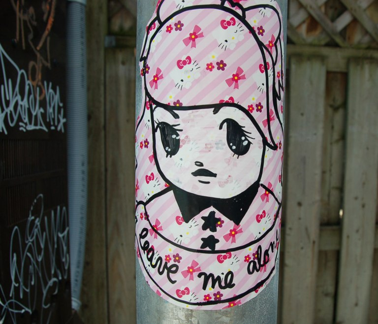 Starchild Stela character, a girl with shoulder length and slightly curly hair, sticker on a grey metal pole, pale pink background with little pink bows pattern, with the words 'leave me alone' written under it