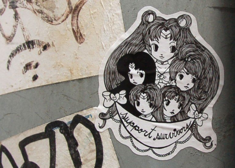 Starchild Stela character, a girl with shoulder length and slightly curly hair, black and white sticker of a number of girls in a group (5) with the words 'support survivors'