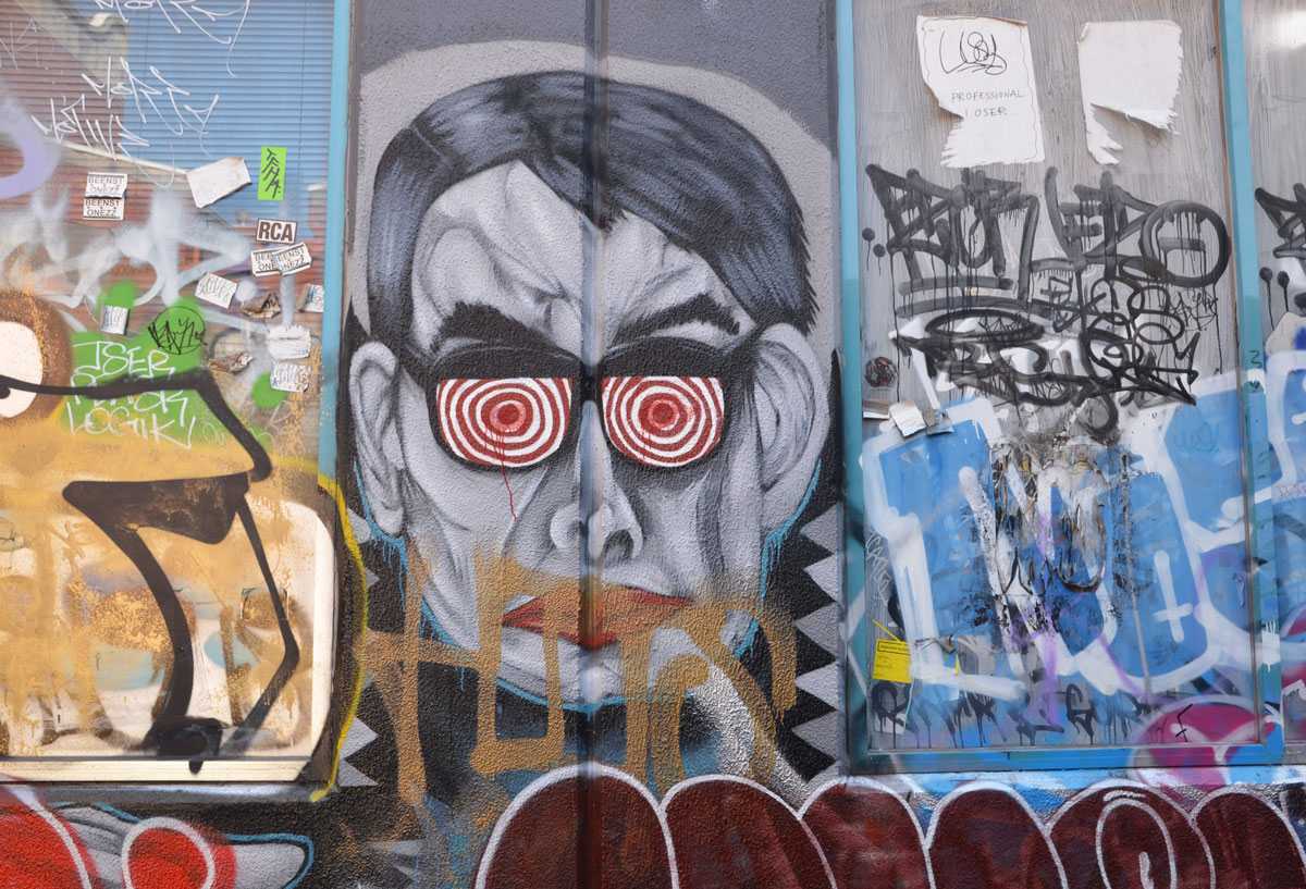 graffiti and street art on a wall, some scrawls and scribbles but also one man's face, wearing glasses with red and white concentric circles instead of lenses