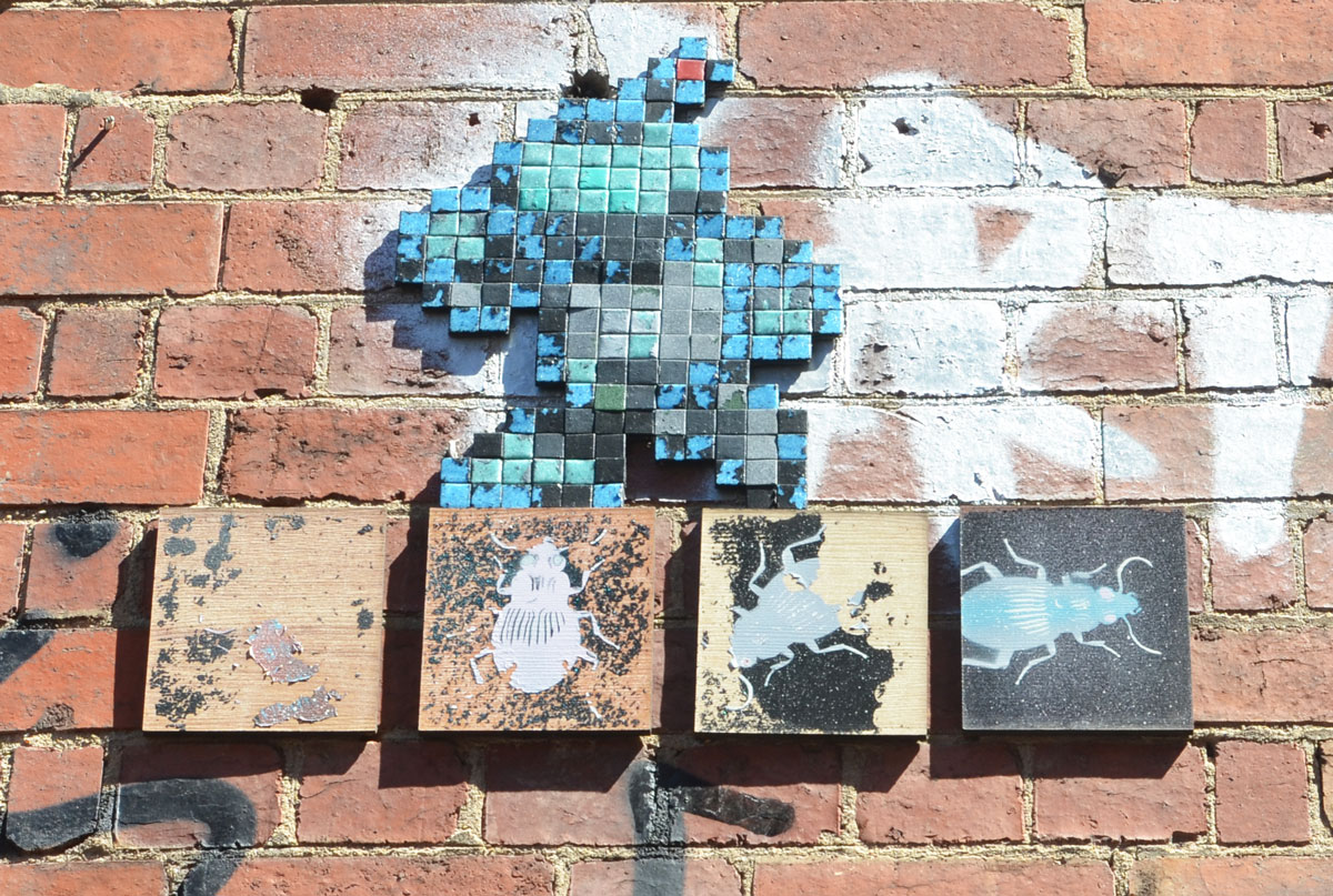 four square pieces of wood mounted on a wall, each with a picture of an insect. Above it is a creature, walking on two legs, made of black and blue mosaic tiles